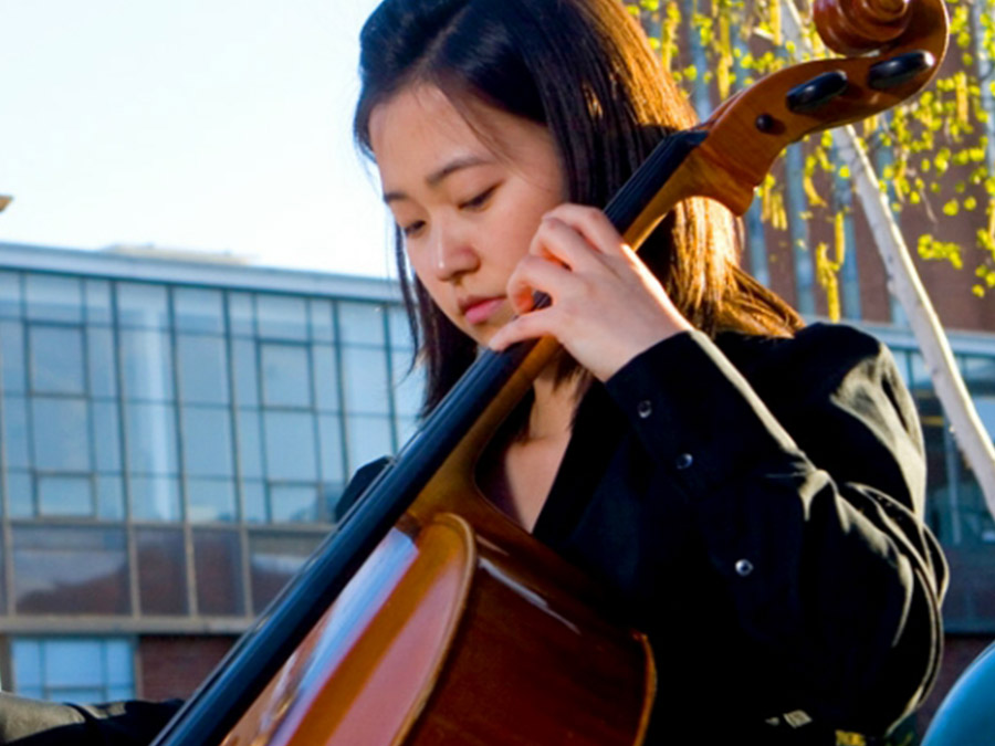 Woman wearing a black coat playing the cello outside