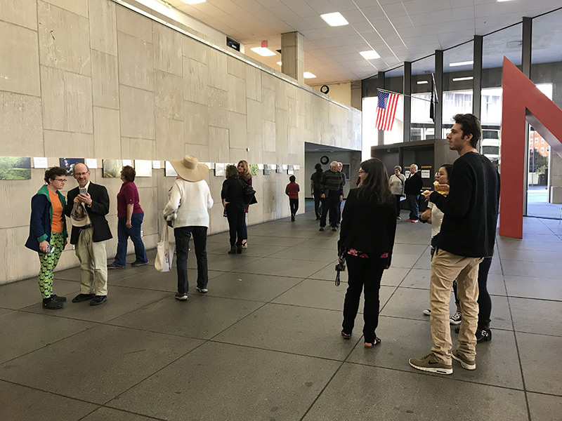 Visitors in the gallery looking at pieces of art on the walls